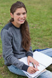 Smiling young woman writing on her notebook Royalty Free Stock Photography