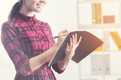 Smiling young woman writing in her notebook royalty free stock photos