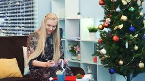 Smiling young woman writing letter near the xmas tree on the New Year`s Eve. She`s sitting on sofa in the living room with beautiful interior and with stock footage