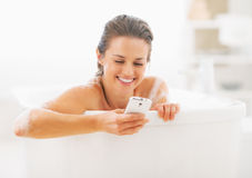 Smiling young woman writing sms in bathtub Stock Photography