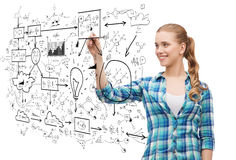 Smiling young woman writing on virtual screen. Happiness and people concept - smiling young woman writing or drawing scheme on transparent screen over white Royalty Free Stock Image