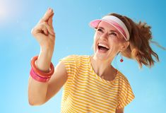 Smiling young woman against blue sky fingers snapping Stock Photography