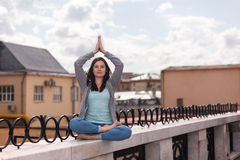 Smiling young woman in a yoga posture on the parapet Stock Photos