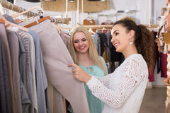 Smiling young women buying pants Stock Images
