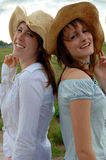 Smiling young women in cowboy hats. Two smiling young women in cowboy hats outdoors stock images