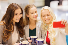 Smiling young women with cups and smartphone Stock Image