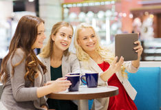 Smiling young women with cups and tablet pc. Drinks, friendship, technology and people concept - happy young women with cups sitting at table and taking selfie Stock Image