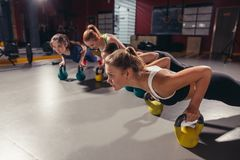 Athletes doing exercises with kettlebells fitness gym