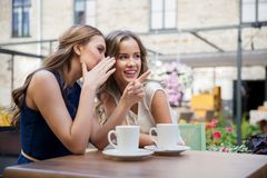 Smiling young women drinking coffee and gossiping. Communication and friendship concept - smiling young women drinking coffee and gossiping at street cafe royalty free stock images