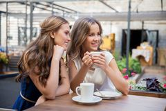 Smiling young women drinking coffee at street cafe Royalty Free Stock Images