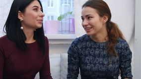 Smiling young women drinking coffee or tea and gossiping stock video footage