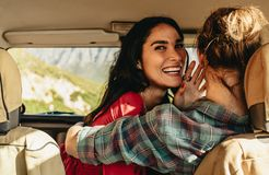 Loving couple in a car on holiday. Smiling young women embracing her boyfriend driving a car. Loving couple in a car on holiday royalty free stock photos