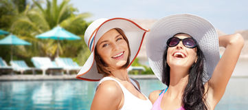 Smiling young women in hats on beach. Summer holidays, vacation, travel and people concept - smiling young women in hats and casual clothes over exotic beach Royalty Free Stock Image
