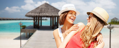 Smiling young women in hats on beach Stock Photos