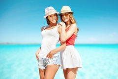 Smiling young women in hats on beach Royalty Free Stock Photography
