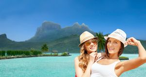 Smiling young women in hats on bora bora beach Stock Image