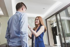 Smiling young woman helping her husband with necktie. Royalty Free Stock Image