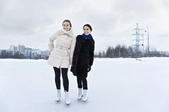 Smiling young women on ice rink Stock Images