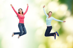 Smiling young women jumping in air Royalty Free Stock Images