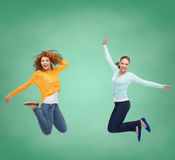 Smiling young women jumping in air Stock Photography