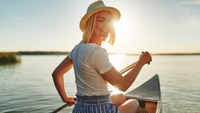 Smiling woman paddling her canoe on a lake in summer royalty free stock images