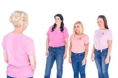 Women in pink t-shirts with ribbons. Smiling young women in pink t-shirts with ribbons looking at senior women isolated on white Stock Photos