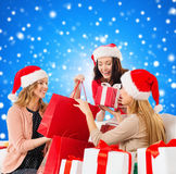 Smiling young women in santa hats with gifts. Sale, winter holidays, christmas and people concept - smiling young women in santa helper hat with gifts and Royalty Free Stock Image