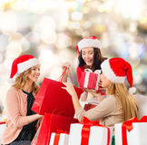 Smiling young women in santa hats with gifts Stock Photography