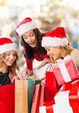 Smiling young women in santa hats with gifts Royalty Free Stock Photo