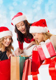 Smiling young women in santa hats with gifts Stock Photo