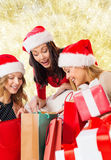 Smiling young women in santa hats with gifts Royalty Free Stock Photography
