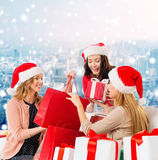 Smiling young women in santa hats with gifts. Sale, winter holidays, christmas and people concept - smiling young women in santa helper hats with gifts and Stock Image