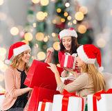 Smiling young women in santa hats with gifts Royalty Free Stock Images
