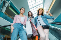 Smiling young women with shopping bags on escalator in shopping mall, young girls shopping concept. Low angle view of smiling young women with shopping bags on Stock Photos