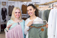 Smiling young women shopping. Smiling european women shopping at the clothing store Stock Photography