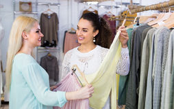 Smiling young women shopping. Smiling young friends shopping at the clothing store Stock Image