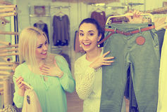 Smiling young women shopping. Smiling young girls shopping at the clothing store Stock Image
