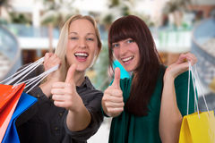 Smiling young women shopping in a shopping mall. Smiling young women with shopping bags having fun while shopping in a shopping mall Royalty Free Stock Images