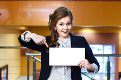 Smiling young women shows on blank white card Royalty Free Stock Images
