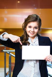 Smiling young women shows on blank white card Royalty Free Stock Image