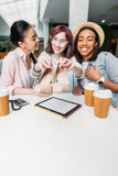 Smiling young women sitting at table with paper cups and showing new stylish shoes. Young girls shopping concept royalty free stock images