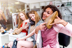 Smiling young women sitting in a womenswear store playing with new footwear using shoes like a phone.  Stock Images