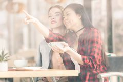 Smiling young women talking and pointing away while drinking coffee together. At lunch meeting stock photos