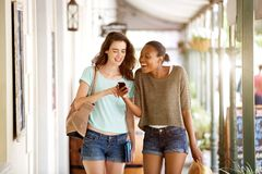 Smiling young women walking together using mobile phone Stock Photo