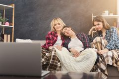 Smiling young women watching movie at home. Smiling young women covered with a blanket relaxing and watching movie on laptop at home, female friends having rest Royalty Free Stock Photography
