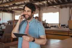 Smiling woodworker talking on his cellphone and using a tablet. Smiling young woodworker with a beard standing in his large carpentry workshop talking on a Royalty Free Stock Photo