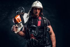 Portrait of muscular man with chainsaw and respirator. Smiling young worker with chainsaw is looking to the camera. He wear helmet and it`s oxygen mask on his stock image