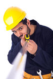 Smiling young worker. Cropped shot of beard young worker holding a measure, guy wearing workwear and yellow helmet with belt equipment, isolated on white Royalty Free Stock Photography