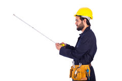 Smiling young worker. Handsome beard young worker looking side and  holding a measure, guy wearing workwear and yellow helmet with belt equipment, isolated on Royalty Free Stock Photo