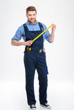 Smiling young worker standing and holding masuring tape Royalty Free Stock Image